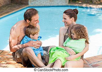 Retrato de una familia feliz junto a la piscina