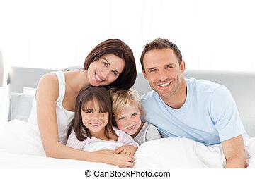 Retrato de una familia feliz sentada en la cama