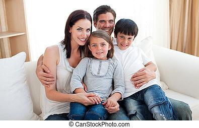 Retrato de una familia sonriente sentada en el sofá