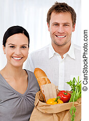 Retrato de una feliz pareja en casa después de comprar