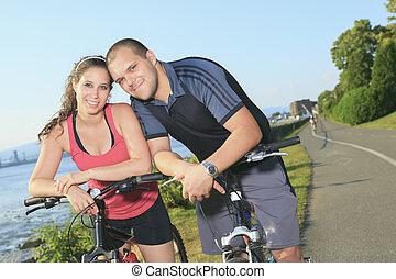 Retrato de una feliz pareja joven en bicicletas de montaña