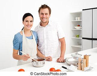 Retrato de una feliz pareja preparando una salsa bolognesa