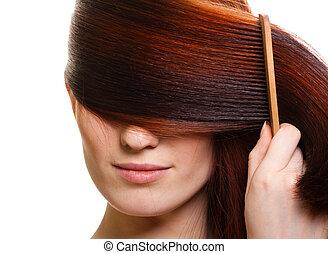 Retrato de una hermosa joven peina un hermoso cabello
