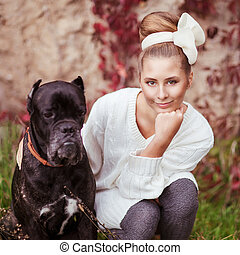 Retrato de una joven abrazando a un gran perro Cane Corso