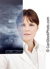 Retrato de una joven doctora caucásica examinando una radiografía