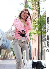Retrato de una joven feliz paseando a su perro en la ciudad y hablando por teléfono