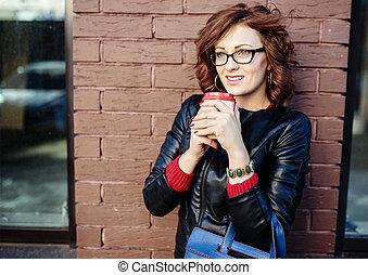 Retrato de una joven moderna con taza de café en las manos, urba