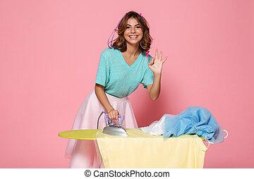 Retrato de una joven sonriente planchando su ropa