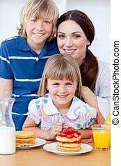 Retrato de una madre y sus hijos desayunando