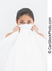 Retrato de una mujer cubriendo la cara con sábanas en la cama