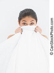 Retrato de una mujer cubriendo la cara con sábanas
