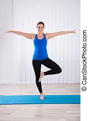 Retrato de una mujer embarazada haciendo yoga