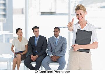 Retrato de una mujer joven haciendo gestos con gente esperando una entrevista de trabajo en una oficina brillante
