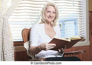 Retrato de una persona mayor mira un álbum de fotos