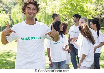 Retrato de voluntarios apuntando a la camiseta