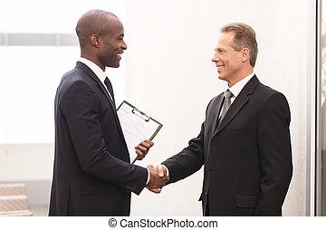 Reunión de negocios. Dos alegres hombres de negocios se dan la mano y se miran