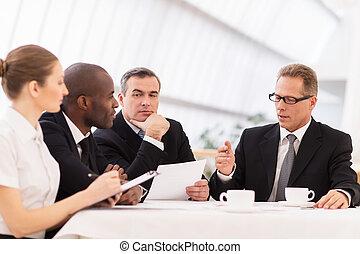 Reunión de negocios. Gente de negocios en ropa formal discutiendo algo mientras se sientan juntos en la mesa