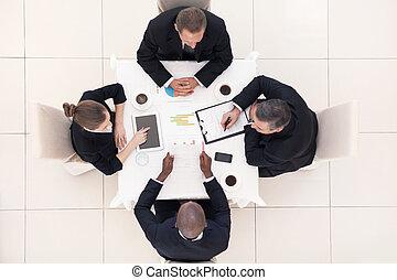 Reunión de negocios. La mejor vista de cuatro empresarios con ropa formal sentados en la mesa y discutiendo algo