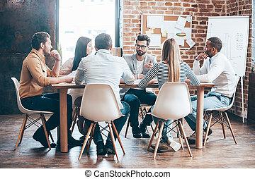 Reunión matutina. Un grupo de seis jóvenes discutiendo algo mientras están sentados en la mesa juntos