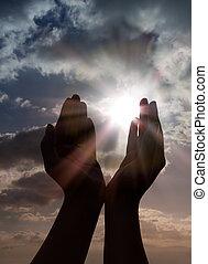 Reza con las manos al sol
