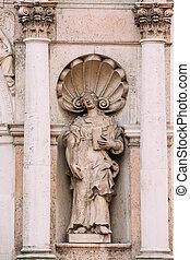 Riga latvia. Una antigua estatua de mujer con un libro abierto entre dos pilares en la fachada de la iglesia St. Peter,