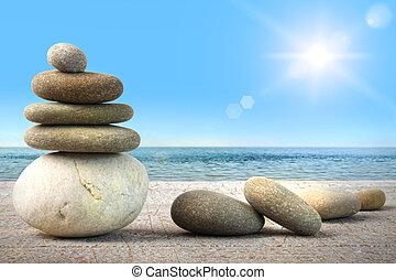 Rocas de spa con madera contra el cielo azul