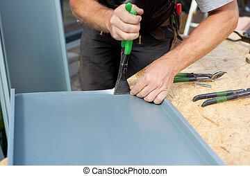 Roofer dobla una hoja de metal usando pinzas especiales