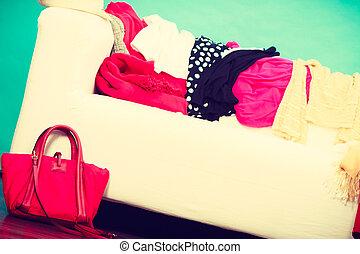 Ropa colorida desordenada tirada en el sofá blanco