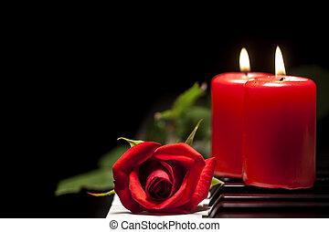 Rosa roja y vela sobre las teclas del piano