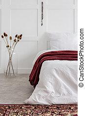 Rosario de madera roja colgando en la pared de una habitación mínima blanca con una cómoda cama y una manta roja, una foto real con espacio de copia en la pared vacía