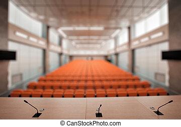 Rostrum con micrófono y computadora en la sala de conferencias. Color naranja