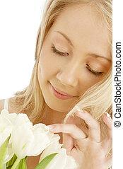 Rubia alegre con tulipanes blancos