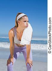 Rubia deportiva parada en la playa con toalla