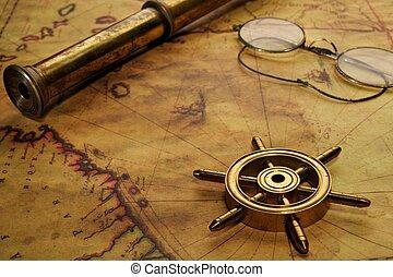 Rueda de dirección, gafas y catalejo en el viejo mapa