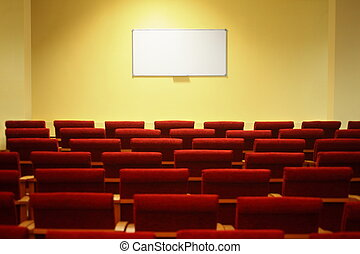 Sala de conferencias vacía con pantalla. Filas de sillas. Enfócate en una pantalla.