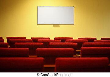 Sala de conferencias vacía. Enfócate en una pantalla. Filas de sillas fuera de foco.