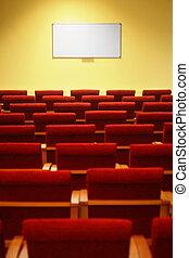 Sala de conferencias vacía. Filas de sillas. Enfócate en una pantalla