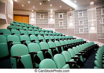 Sala de conferencias vacías, filas de sillas, ocho números en escena