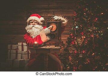 Santa Claus en el interior de la casa de madera mostrando tiempo en un reloj