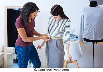 Sastre atento mide la cintura de una mujer muy delgada