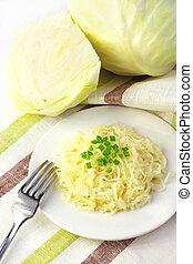 Sauerkraut en el plato blanco y cabeza de repollo blanco