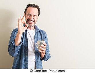 Señor bebiendo café en una taza haciendo bien signo con dedos, excelente símbolo