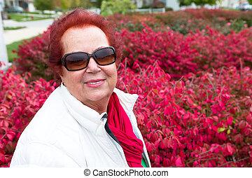 Señora mayor disfrutando de los arbustos en llamas