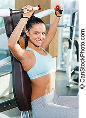 Se siente confiada en su cuerpo perfecto. Una joven atractiva mirando a la cámara y sonriendo mientras hacía ejercicio en el gimnasio