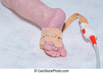 Sensor de oxígeno en el pie del bebé recién nacido en el hospital infantil