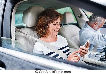 sentado, 3º edad, smartphone, yendo, coche, trip., par bueno