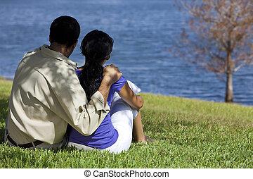 sentado, pareja, lago, norteamericano, africano, vista trasera