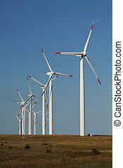 Series de generadores de energía eólica en un campo de hierbas