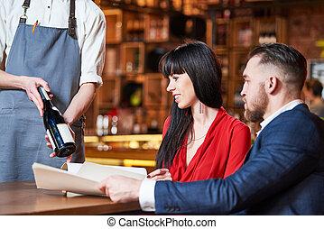 Servicio de restaurantes. Una pareja joven y un camarero ofrecen una botella de vino