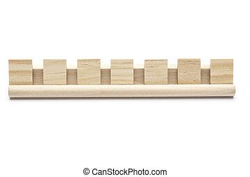 Siete azulejos de scrabble en un estante de madera, en fondo blanco